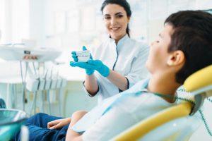 female-dentist-shows-dentures-to-little-boy-QL97ED4