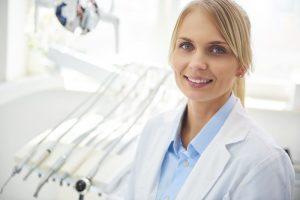 portrait-of-smiling-dentist-in-medical-uniform-in - 5WSQLTE
