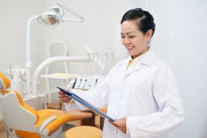 smiling-dentist-reading-clipboard-in-office-JN4YAUV (1)