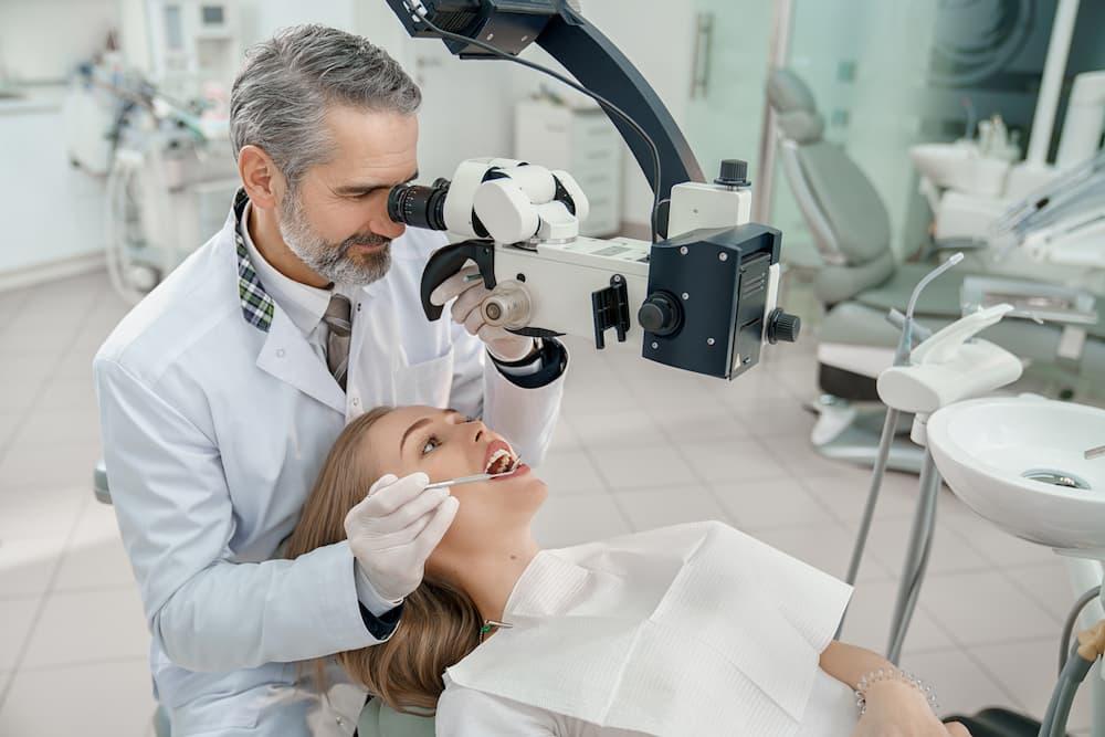 doctor-looking-through-dental-microscope-at-teeth--CQTD9N6 (1)
